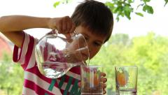 Stock Video Footage of boy pours water from a jug into glasses on the nature