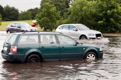 Cars trying to drive against flood on the street in Gdansk, Poland. - stock photo