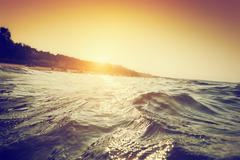 Sea waves and ripples at sunset. First person perspective swimming - stock photo