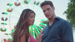 A couple looking at the camera and being romantic in front of a ferris wheel - stock footage
