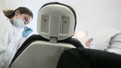 Shot from behind dental chair, dentist and assistant prepare for exam Stock Footage