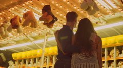 Portrait of a couple in front of a carnival arcade game - stock footage