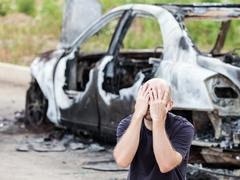 Crying upset man at arson fire burnt car vehicle junk - stock photo