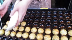 Cooking takoyaki is a ball-shaped Japanese snack at Dotonbori in Osaka, Japan Stock Footage