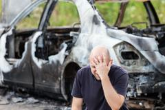 Crying upset man at arson fire burnt car vehicle junk Stock Photos