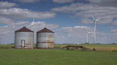 Windmill turbines generating energy behind grain silos - stock footage