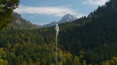 Bavarian Alps with water foreground, tilt down to fountain Stock Footage