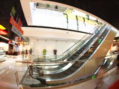 Blurred image of a large shopping mall hall with escalator Kuvituskuvat
