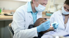 Dentist and his dental nurse inspect patient's mouth and exchange words Stock Footage