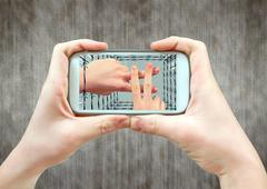 Hand gesture on the screen of a smartphone in the prison bars - stock photo