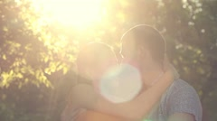 Romantic young couple in love sit together in park at sunset light background. Stock Footage