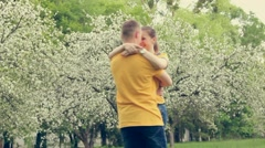 Cute young couple in love spinning around together in spring blooming garden Stock Footage