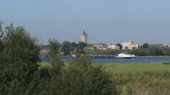 Gorinchem city skyline alongside river Merwede + inland ship moves downstream Stock Footage
