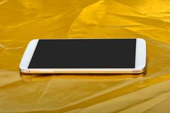 Smartphone Reflection on Golden Background - stock photo