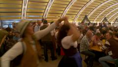 Octoberfest Munich beer hall - women dancing under tent, pan right - stock footage