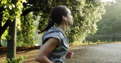Runner woman running in park exercising outdoors fitness tracker wearable - stock footage