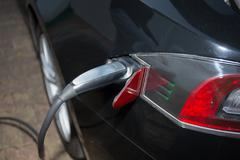 Black electric car charging: Close-up of indistinguishable electric car 'fuel - stock photo