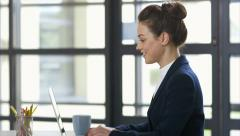 Side view of smiling businesswoman using laptop in office Stock Footage
