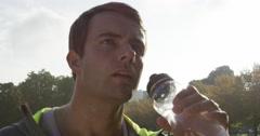Runner man drinking water bottle sun flare solar energy Stock Footage