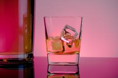 one glass of whiskey with ice cubes near bottle on table with reflection, lig - stock photo