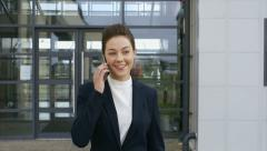 Beautiful businesswoman using mobile phone while leaving from office Stock Footage