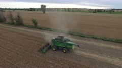 4k aerial farm combine harvesting crops in field - stock footage