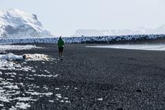 Woman walks along black sand beach in Vik, Iceland - stock photo