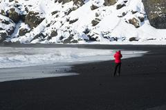 Photographer at the black sand beach in Vik, Iceland Stock Photos