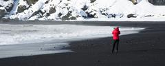 Photographer at the black sand beach in Vik, Iceland - stock photo