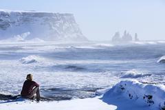 Woman enjoys view o three pinnacles of Vik, Iceland - stock photo