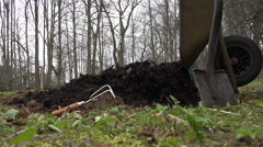 Gardener unload barrow with compost on vegetable bed. 4K - stock footage
