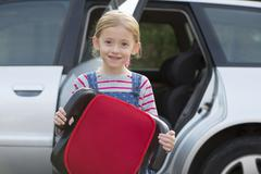 Portrait Of Girl Holding Booster Seat Standing Next To Car Stock Photos