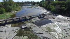 4k aerial over river bed and crumbled train bridge - stock footage