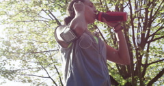 Runner woman drinking water bottle sun flare solar energy Stock Footage