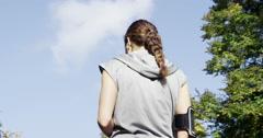 Runner woman drinking water bottle sun flare solar energy Stock Footage