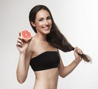 Portrait of woman promoting healthy eating. Beautiful young brunette woman wi - stock photo