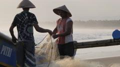 Fishermen unloading net on beach,Pangandaran,Java,Indonesia Stock Footage