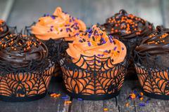 Orange and dark chocolate Halloween cupcakes - stock photo