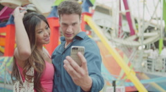 A couple taking selfies in front of a ferris wheel Stock Footage