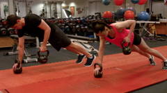Couple doing weighted plank rows in gym Stock Footage