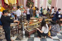 People burn candles in Nakhom Pathom chedi, Nakhom Pathom, Thailand. Stock Photos