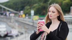 Cheerful gorgeous brunette holding disposable cup on urban background Stock Footage