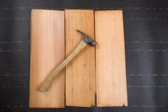 Used roofing hammer with new cedar wood shingles on felt paper - stock photo