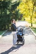 Woman with stroller going for a walk - stock photo