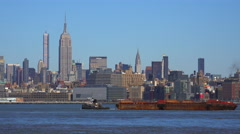 A tugboat pulls a barge on the Hudson River in New York City with the Empire Stock Footage