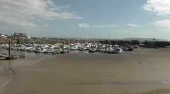 Burry Port harbour at low tide with the lighthouse in the background Stock Footage