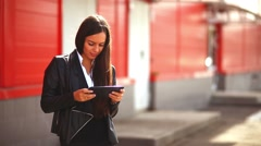 brunette girl playing on tablet in the street woman behind a red background - stock footage