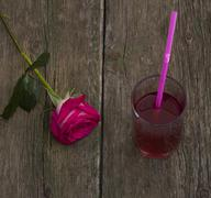 one red rose and glass of juice, on an old table - stock photo