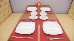 Served tables waiting for clients mugs spoons forks plates napkins on the table - stock footage