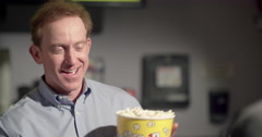 Grinning concession stand employee serves popcorn 4K Stock Footage